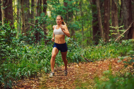 sportive: Attractive Young Woman Running in the Forest