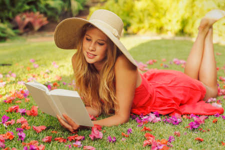 Beautiful Young Woman Reading a Book Outside on the Grass Stock Photo