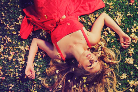 lying on grass: Beautiful Young Woman Lying on Grass with Flowers In Red Dress