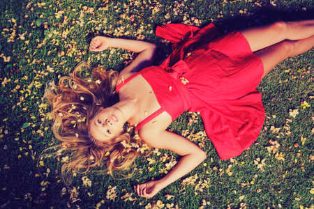 Beautiful Young Woman Lying on Grass with Flowers In Red Dress photo