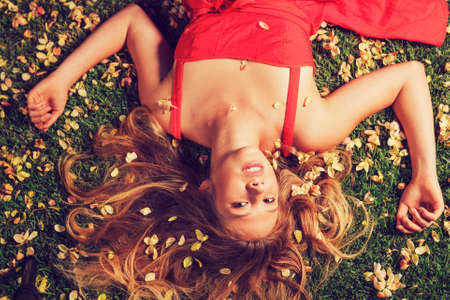 Beautiful Young Woman Lying on Grass with Flowers In Red Dress Stock Photo - 15871944