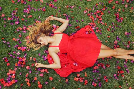 美しい若い女性は赤いドレスを着ての花の草の上に横たわる