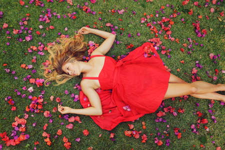fashion make up: Beautiful Young Woman Lying on Grass with Flowers In Red Dress