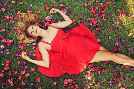 red grass: Beautiful Young Woman Lying on Grass with Flowers In Red Dress