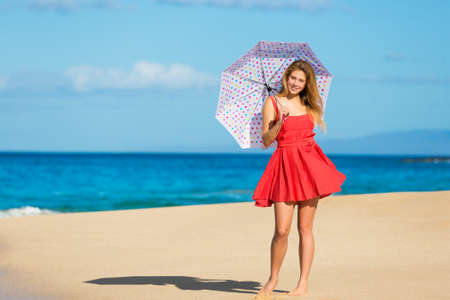 Beautiful Young Woman Walking on Tropical Beach with Colorful Umbrella photo