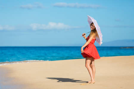 Beautiful Young Woman Walking on Tropical Beach with Colorful Umbrella Фото со стока