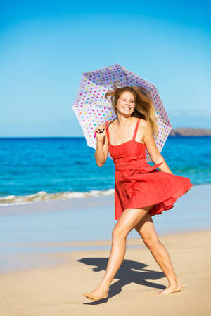 Beautiful Young Woman Walking on Tropical Beach with Colorful Umbrella Banco de Imagens