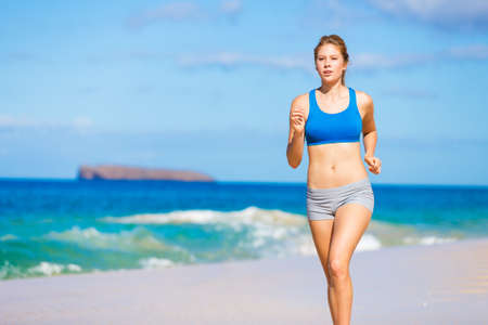 Running woman. Female runner jogging during outdoor workout on beach. Beautiful Fitness Model Outdoors. photo