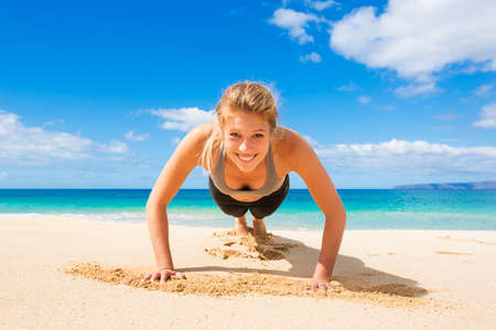 push: Attractive Young Woman Doing Push Up Exercise on the Beach