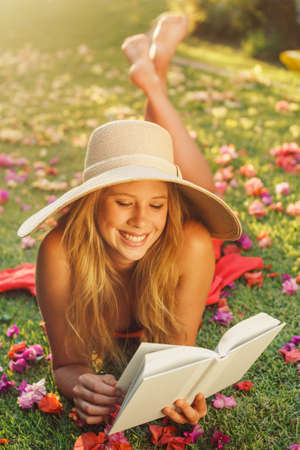 Beautiful Young Woman Reading a Book Outside on the Grass Stock Photo - 15977960
