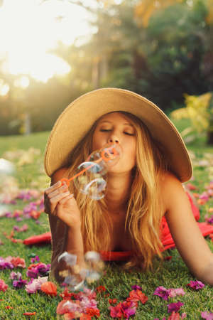 Beautiful Young Woman Blowing Bubbles photo