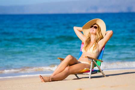 Jonge mooie vrouw op het strand ontspannen in de zon