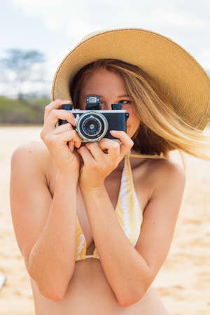 Beautiful Young Woman at the Beach with Vintage Camera photo