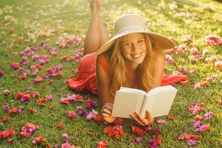 mujer leyendo libro: Mujer hermosa joven que lee un libro afuera en la hierba