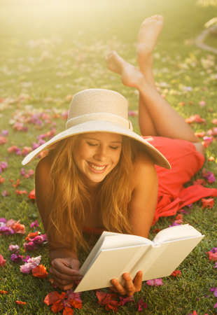 Beautiful Young Woman Reading a Book Outside on the Grass Archivio Fotografico