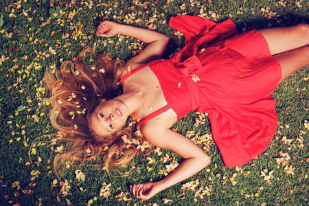 Beautiful Young Woman Lying on Grass with Flowers Stock Photo