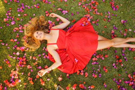 Beautiful Young Woman Lying on Grass with Flowers photo