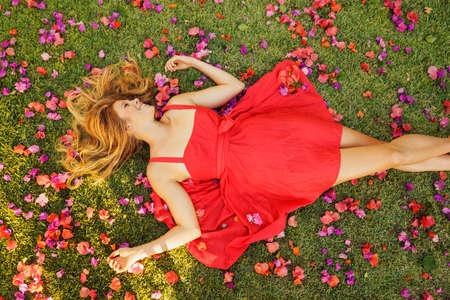 美しい若い女性は花と草の上に横たわる 写真素材