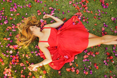 Beautiful Young Woman Lying on Grass with Flowers 스톡 콘텐츠