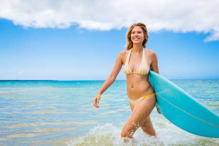 Hermosa mujer joven en bikini Chica surfista con tabla de surf en una playa