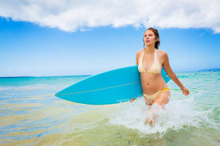 surf girl: Beautiful Young Woman Surfer Girl in Bikini with Surfboard at a Beach Stock Photo