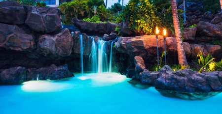 hawaii sunset: Tropical Resort Pool and Waterfall at Sunset in Hawaii Stock Photo