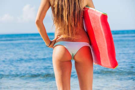 Young beautiful woman enjoying the sun on the beach, with boogie board and sexy bikini