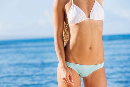 Young beautiful woman enjoying the sun on the beach, sexy bikini