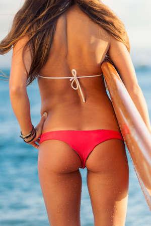 wet bikini: Beautiful young woman with surfboard in sexy bikini