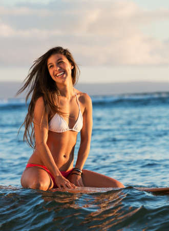 beautiful young woman on surfboard at sunset in ocean, waiting for a wave in hawaii