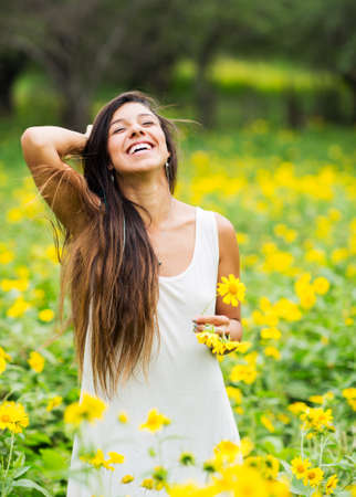 tall grass: Beautiful young woman in a field of yellow flowers Stock Photo