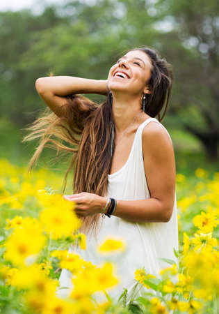 feelings of happiness: Beautiful young woman in a field of yellow flowers Stock Photo