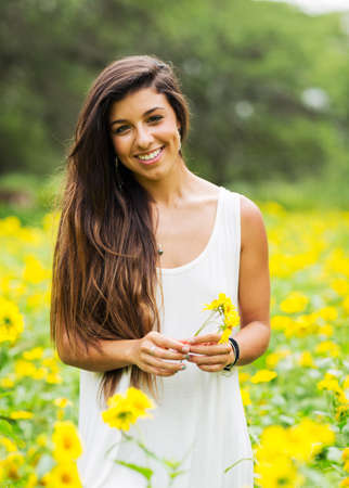 Beautiful young woman in a field of yellow flowers 免版税图像