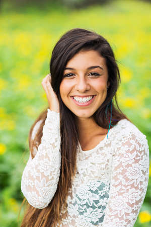 Outdoor portrait of a beautiful young brunette woman smiling happy