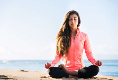 anti stress: Young woman practicing morning meditation in nature at the beach Stock Photo