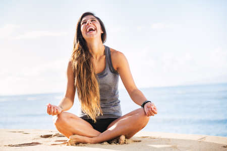 breath: Young woman practicing morning meditation in nature at the beach Stock Photo