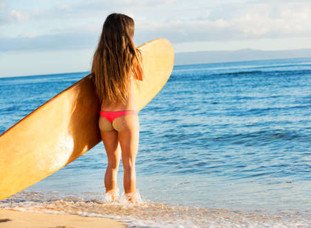 beautiful sexy young woman surfer girl in bikini with surfboard on a beach at sunset photo