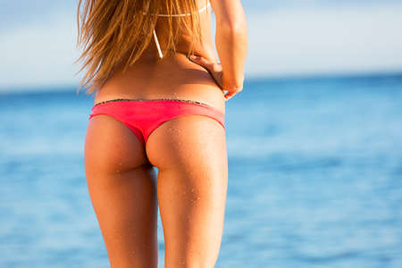 Rear view of beautiful sexy young woman surfer girl in bikini on a beach at sunset photo