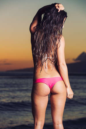 young sexy woman in bikini at the beach at sunset photo