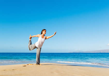 Beautiful young woman stretching during yoga on the beach photo