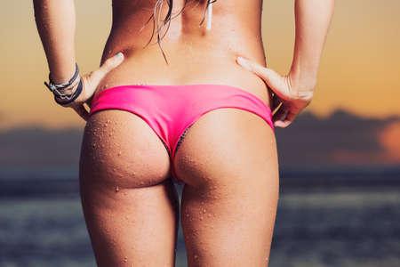 young sexy woman in bikini at the beach, thong bikini photo