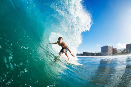 Surfer on Blue Ocean Wave Getting Barreled Stock Photo