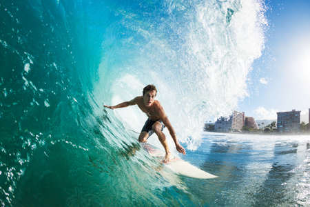 in action: Surfer on Blue Ocean Wave Getting Barreled Stock Photo