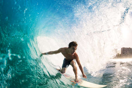 surfing beach: Surfer on Blue Ocean Wave Getting Barreled Stock Photo
