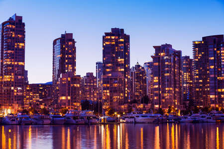 Modern Urban City Skyline Reflecting in Water at Sunset, Vancouver photo
