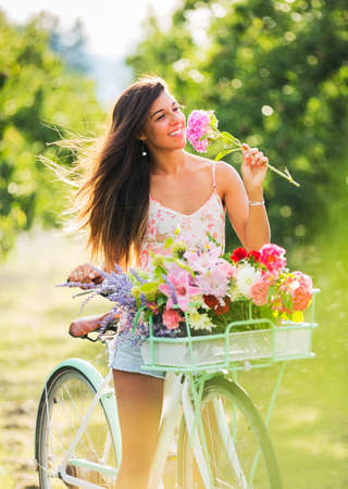 Beautiful Girl on Bike in Countryside Smelling Flowers, Summer Lifestyle  photo