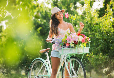 mooie vrouwen: Mooi Meisje op fiets in Countryside ruikende bloemen, Zomer Lifestyle