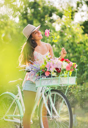 Beautiful Girl on Bike in Countryside Smelling Flowers, Summer Lifestyle  Stock Photo - 21512152