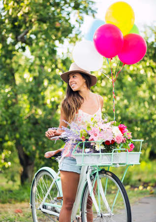 Beautiful Girl on Bike with Balloons in Countryside, Summer Lifestyle  photo
