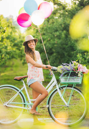 Hermosa chica en la bici con globos en el campo, estilo de vida Summer